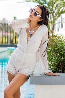 Giovane modello abbronzatura in abito estivo alla moda che gode della festa in piscina accessori boho, occhiali da sole alla moda.