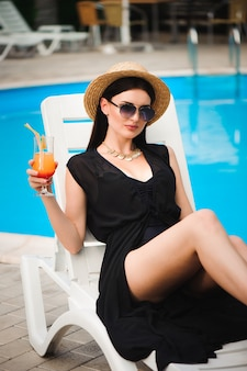 Young tan model in stylish summer outfit enjoying pool party , holding tasty alcohol cocktail