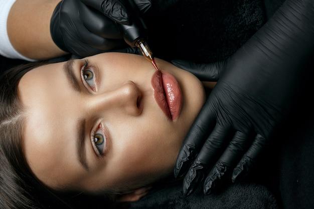 美容スタジオで唇の恒久的な手順を持っている若い日焼けしたブルネットの女性。上面図