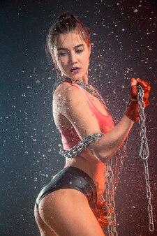 Молодая загорелая подтянутая женщина с красивыми спортивными ягодицами и тонкой талией с каплями воды в студии с железными цепями