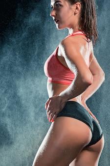 Молодая загорелая подтянутая женщина с красивыми спортивными ягодицами и тонкой талией с каплями воды в студии