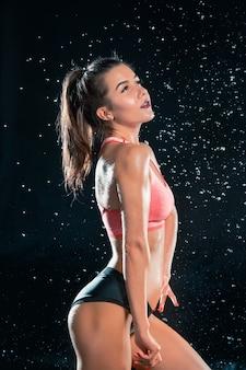 Молодая загорелая подтянутая женщина с красивыми спортивными ягодицами и стройной с каплями воды