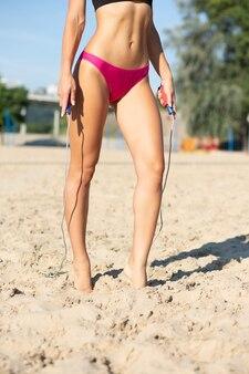 ビーチで縄跳びでストレッチをしている完璧なボディを持つ若い日焼けモデル