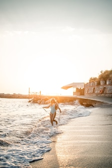 A young tanned woman in a beautiful swimsuit with a straw hat stands and rests on a tropical beach with sand and looks at the sunset and the sea. selective focus. vacation concept by the sea
