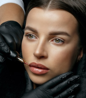 Молодая загорелая женщина, имеющая постоянное окрашивание губ в студии красоты. снимок крупным планом