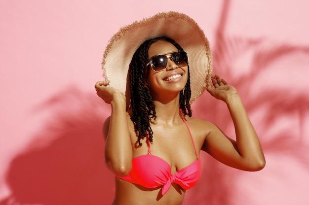 Молодая загорелая женщина в купальнике, шляпе и солнцезащитных очках на розовом