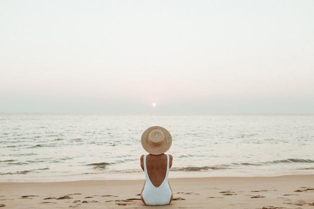 麦わら帽子と美しい白い水着を着て日焼けした若い女性は、白い砂浜の熱帯のビーチに座ってリラックスし、夕日と海を見ています