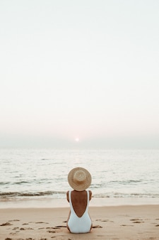 Young tanned woman wearing a beautiful white swimsuit with a straw hat is sitting and relaxing on tropical beach with white sand and is watching sunset and sea