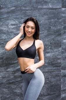 Молодая загорелая женщина в спортивной одежде серая вершина, стоящая у стены.