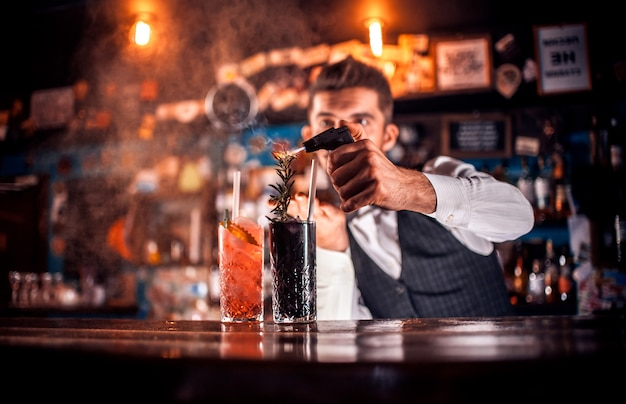 Young tapster makes a cocktail in cocktail bars