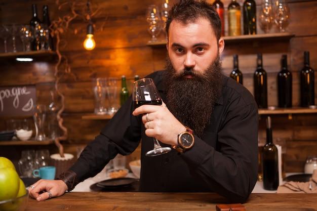 Молодой татуированный бармен с большой бородой дегустирует бокал вина. хипстерский паб.