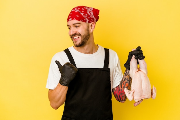 親指の指を離れて、黄色の背景のポイントで隔離された鶏を保持し、笑ってのんきな若い入れ墨のバッチャー白人男性。