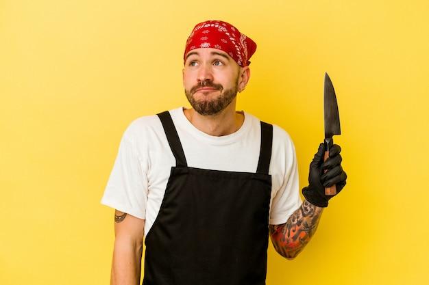 목표와 목적을 달성하는 꿈을 꾸고 노란색 배경에 고립 된 칼을 들고 젊은 문신 된 batcher 백인 남자