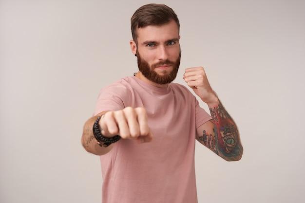Молодой татуированный брюнет с бородой, угрожающе поднимающий кулак, читается, чтобы драться, позирует на белом в повседневной одежде
