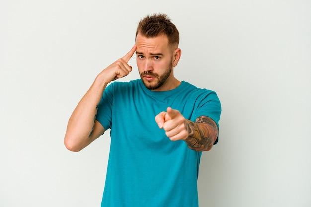 젊은 문신 된 백인 남자 손가락으로 사원을 가리키는 흰색 배경에 고립 생각, 작업에 초점을 맞춘.