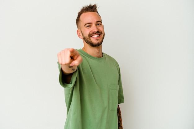 指で正面を指している白い背景に分離された若い入れ墨の白人男性。