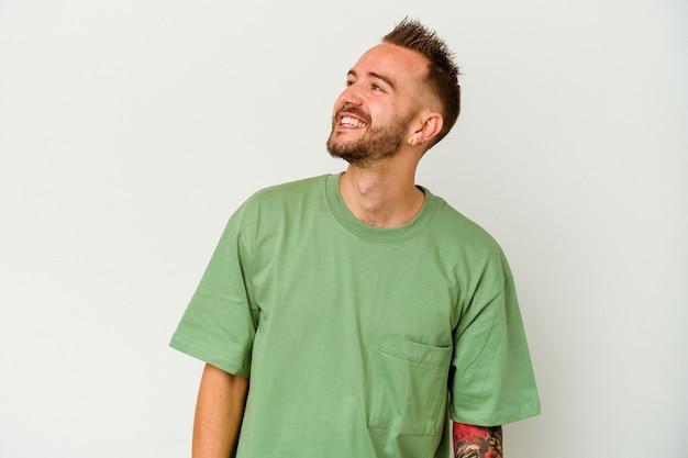 Молодой татуированный кавказский человек, изолированные на белом фоне, расслабленный и счастливый смех, вытянув шею, показывая зубы.