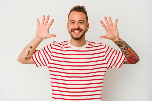 Молодой татуированный человек кавказской изолирован на белом фоне, показывая номер десять руками.