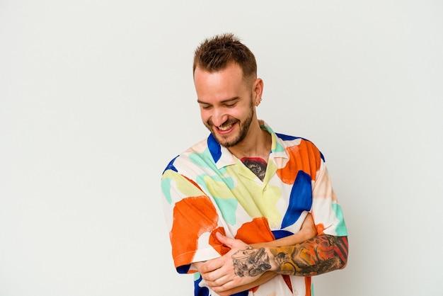젊은 문신 된 백인 남자 교차 팔 자신감 웃 고 흰색 배경에 고립.