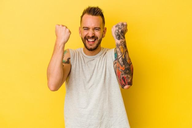 젊은 문신 된 백인 남자 평온한 및 흥분 응원 노란색 배경에 고립. 승리 개념.