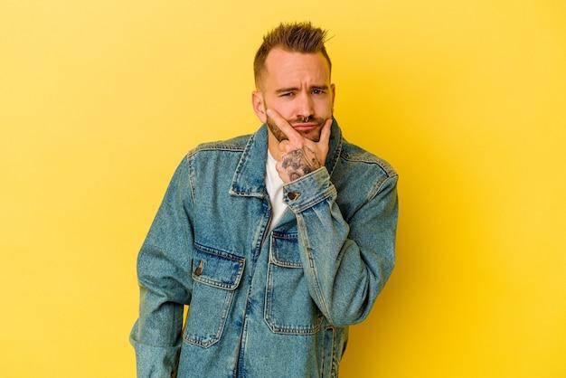 젊은 문신 백인 남자 고민, 전략 계획, 사업 방법에 대해 생각하는 노란색 배경에 고립.