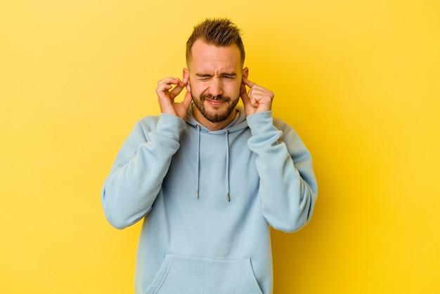 指で耳を覆っている黄色の背景に隔離された若い入れ墨の白人男性は、大声で周囲によってストレスと絶望的です。