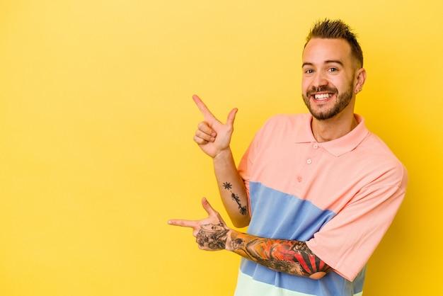 Молодой татуированный мужчина кавказской изолирован на желтом фоне возбужденно указывая указательными пальцами.