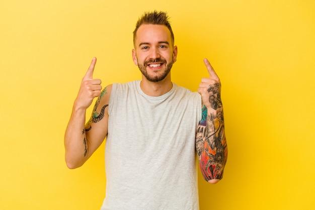 노란색 배경에 고립 된 젊은 문신 된 백인 남자는 빈 공간을 보여주는 두 앞 손가락으로 나타냅니다.