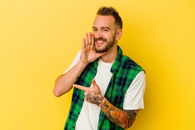 젊은 문신 된 백인 남자는 험담을 말하는 노란색 배경에 고립 뭔가보고 측면을 가리키는.