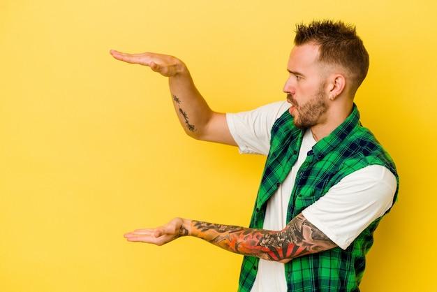 노란색 배경에 고립 된 젊은 문신 된 백인 남자 충격과 손 사이의 복사본 공간을 잡고 놀 랐 어 요.