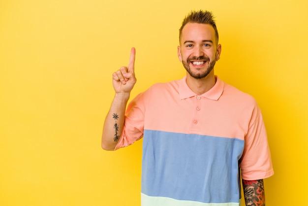 指でナンバーワンを示す黄色の背景に分離された若い入れ墨の白人男性。