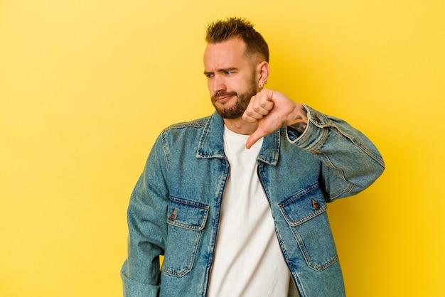 젊은 문신 된 백인 남자 아래로 엄지 손가락을 표시 하 고 싫어하는 표현 노란색 배경에 고립.