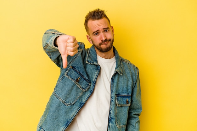 親指を下に向けて、失望の概念を示す黄色の背景に分離された若い入れ墨の白人男性。