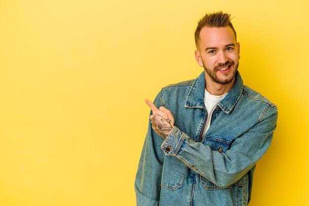 젊은 문신 된 백인 남자 웃 고 옆으로 가리키는 노란색 배경에 고립 된 빈 공간에서 뭔가 보여주는.