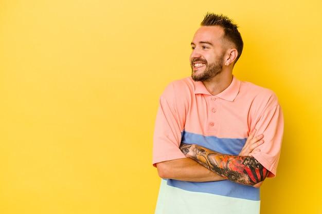 젊은 문신 된 백인 남자 교차 팔 자신감 웃 고 노란색 배경에 고립.