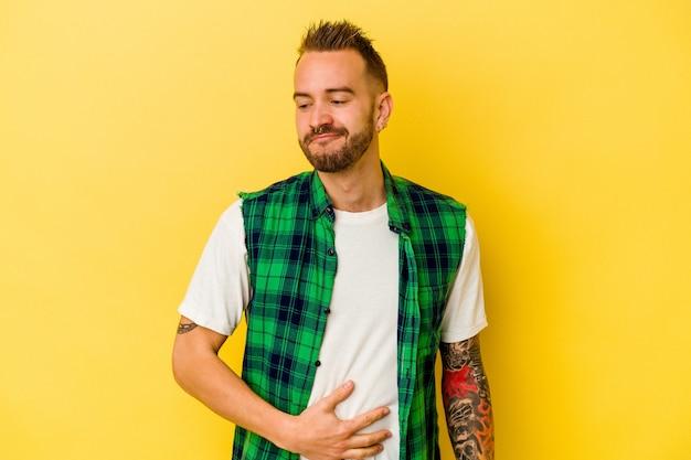 노란색 배경에 고립 된 젊은 문신 된 백인 남자는 배를 만지고, 부드럽게 미소, 식사 및 만족 개념.