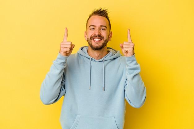 노란색 벽에 고립 된 젊은 문신 된 백인 남자는 빈 공간을 보여주는 두 앞 손가락으로 나타냅니다.