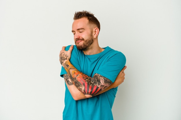Young tattooed caucasian man isolated on white background hugs, smiling carefree and happy.