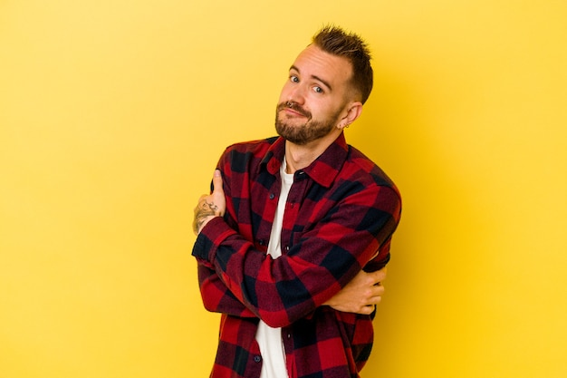 Young tattooed caucasian man isolated on yellow background hugs, smiling carefree and happy. Premium Photo