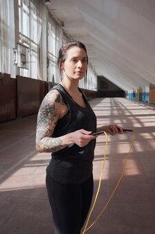 Молодая татуированная спортсменка в черной спортивной одежде стоит со скакалкой в зале и задумчиво смотрит вдаль