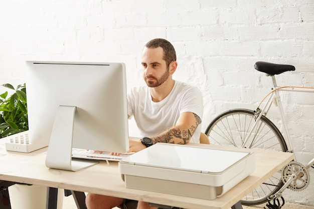 Young tattooed freelancer man in blank white t-shirt works on his computer at home near his bicycle, looking in display
