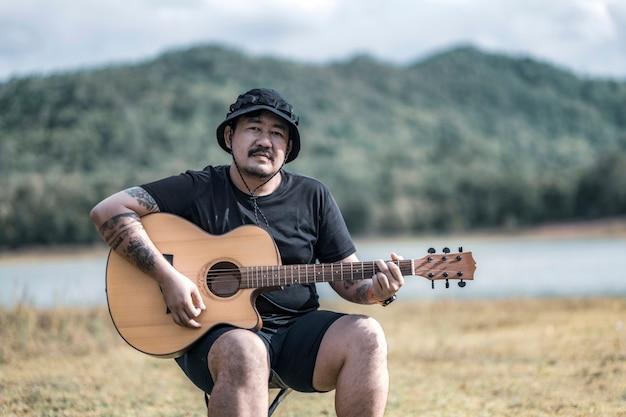 아름다운 일몰 동안 여름 들판에서 어쿠스틱 기타를 연주하는 문신을 한 젊은 남성