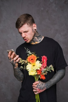 Young tattooed and pierced man holding flower bouquet in hand making face while using mobile phone