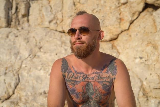 Giovane uomo sportivo tatuato sulla spiaggia in una calda giornata di sole estivo in montagna in posa con gli occhiali da sole