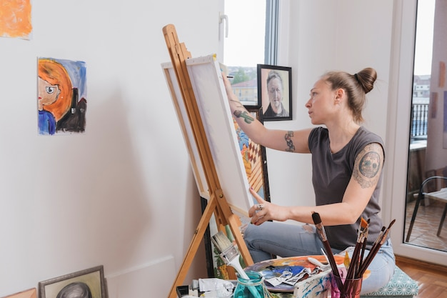 Young tattooed woman painting picture sitting in art studio