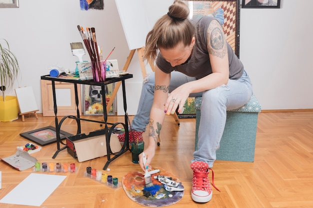Young tattooed woman sitting on stool mixing colors on palette