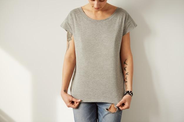 Giovane donna tatuata che indossa la maglietta in bianco grigia