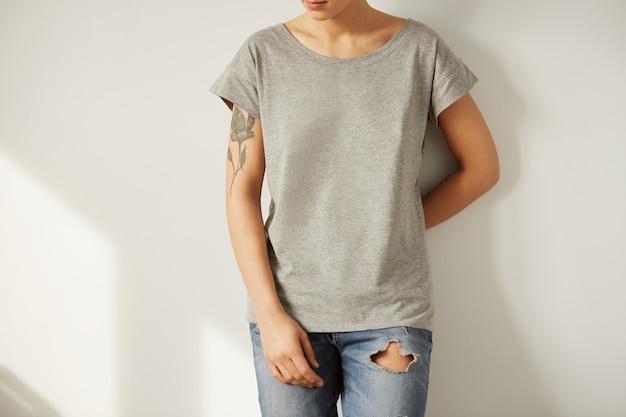 회색 공백 t- 셔츠를 입고 젊은 문신 된 여자