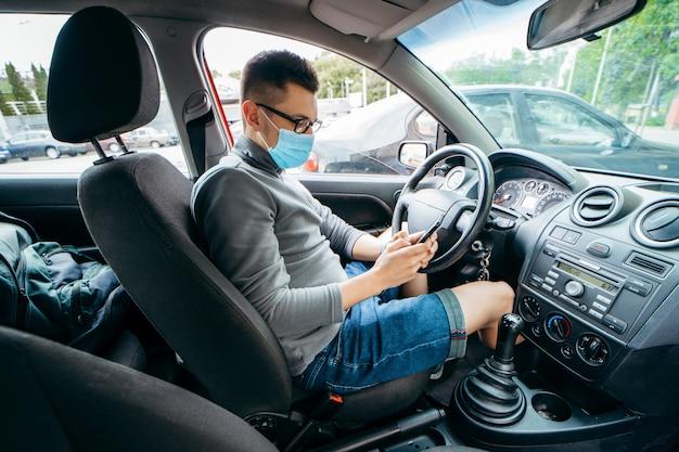 彼の手でスマートフォンを持つ医療マスクの若いタクシードライバー
