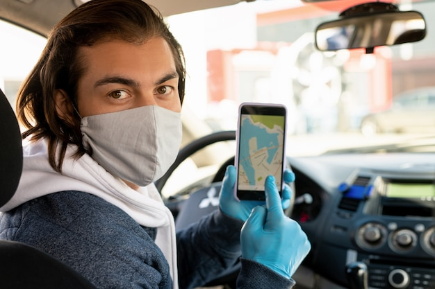Young taxi driver in protective mask and gloves pointing at smartphone screen